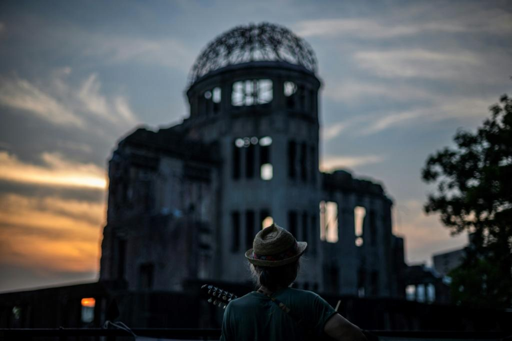 A man plays his guitar in front of the Hiroshima Prefectural Industrial Promotion Hall, now commonly known as the atomic bomb dome