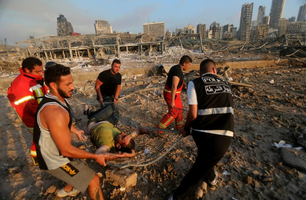 Lebanese firefighters evacuate a wounded man across the rubble of buildings flattened by the force of the monster blast in Beirut port