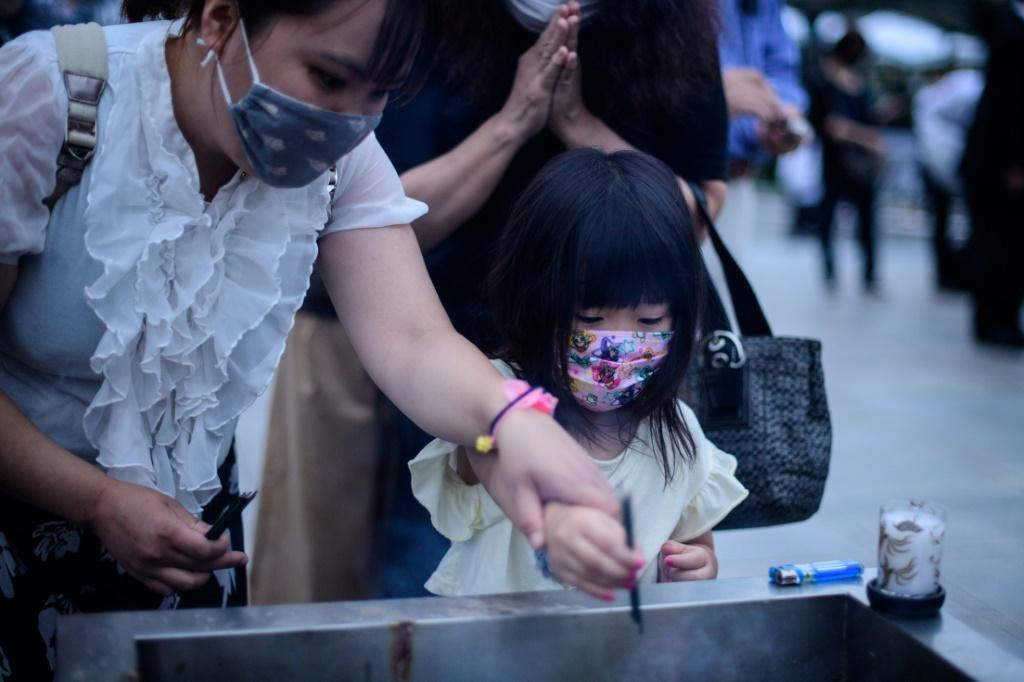 Visitors burn incense at the Hiroshima Peace Memorial Park to mark 75 years since the world's first atomic bomb attack