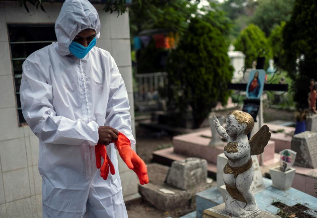 A gravedigger gets ready to work during a funeral at the San Isidro cemetery in Azcapotzalco, in Mexico City on August 6, 2020, amid the COVID-19 coronavirus pandemic.