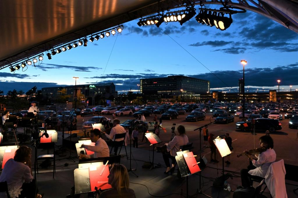 """The Montreal Symphony Orchestra performs in a parking lot at Trudeau International Airport on August 5, 2020 during a socially distanced """"drive-in"""" concert"""