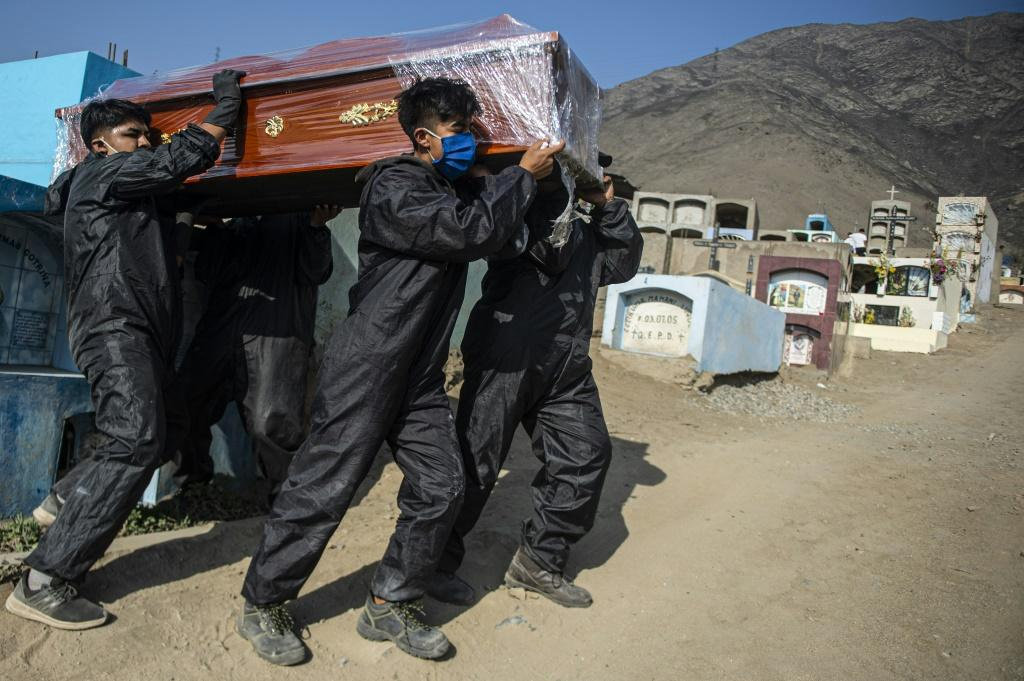 Cemetery workers carry the coffin of a COVID-19 victim at a graveyard in Comas, in the northern outskirts of Lima.