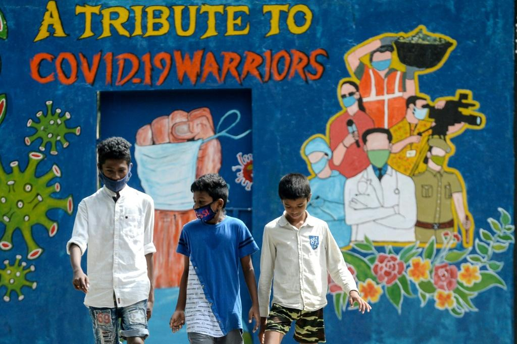 Youths walk past a mural dedicated to frontline workers fighting against the spread of the COVID-19 coronavirus, in Chennai.