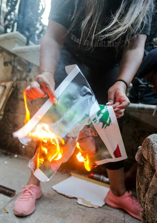 A Lebanese protester in the ministry burns a picture of President Michel Aoun