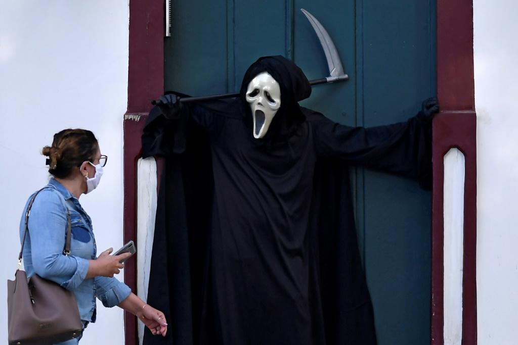 A woman looks at Brazilian actor Fabio de Almeida disguised as death to raise awareness of the importance of wearing face masks and social distancing, in Formiga, Minas Gerais