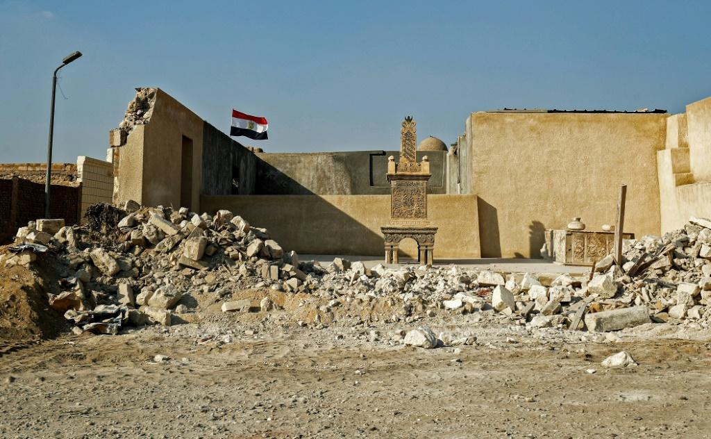 An Egyptian flag behind a grave marker, exposed by the destruction of a surrounding wall in the historic City of the Dead necropolis in Egypt's capital Cairo