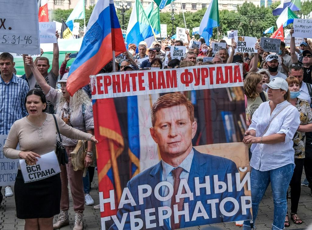 """Protestors in the Russian Far East city of Khabarovsk carry a banner reading """"Return Furgal for us"""", during an unauthorised rally Saturday in support of Sergei Furgal"""