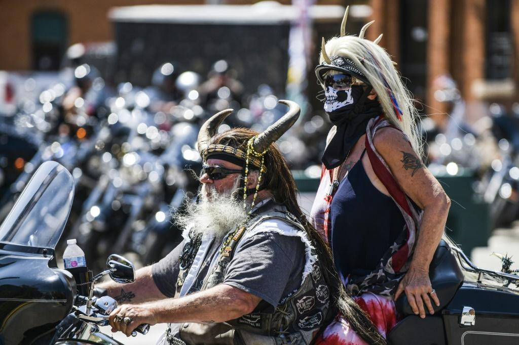 Two cyclists ride down the Main Street in Sturgis, South Dakota, on August 7, 2020 as part of the huge motorcycle rally there