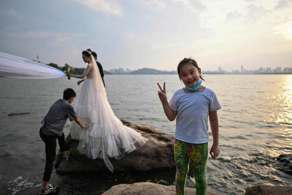 A girl gestures while a couple poses for a wedding photographer next to East Lake in Wuhan