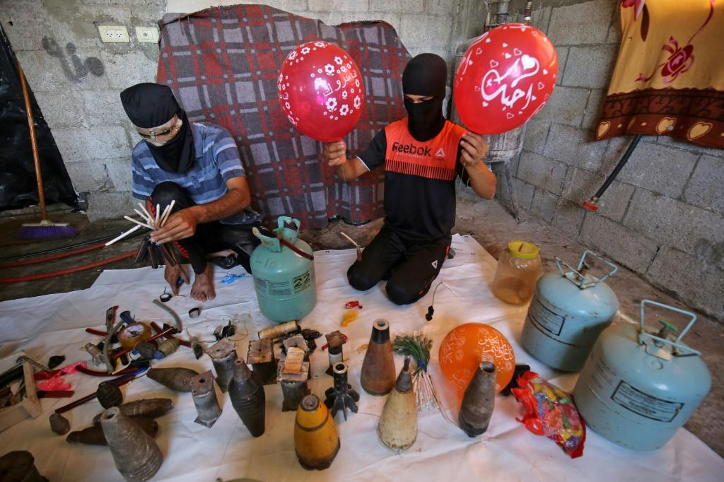 Masked Palestinians prepare flammable objects before attaching them to balloons to be flown towards Israel, in Rafah in the southern Gaza Strip