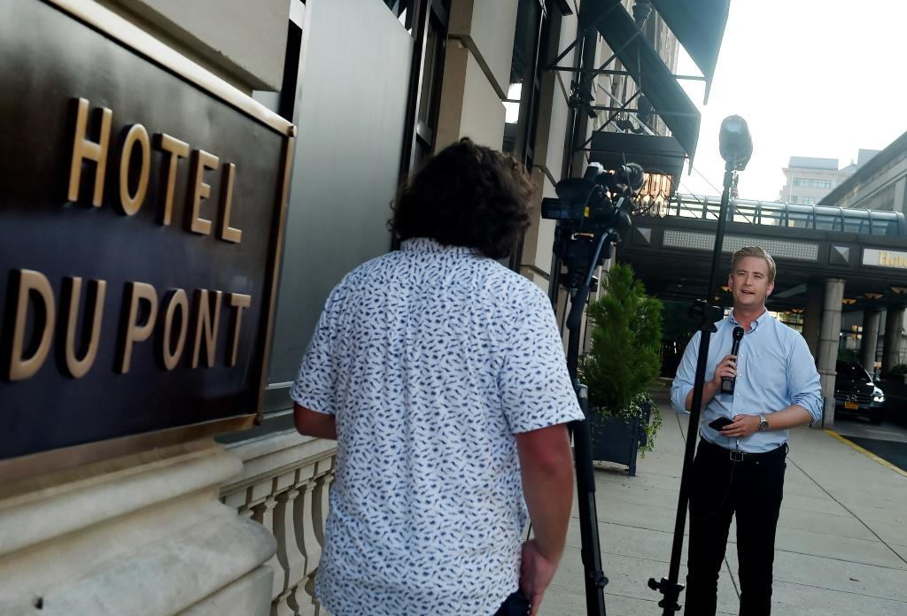 A reporter and cameraman do a live shot outside Hotel du Pont in Wilmington, Delaware, after Democratic presidential nominee Joe Biden named US Senator Kamala Harris of California as his running mate in the 2020 presidential race