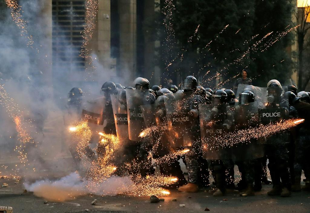 Firecrackers thrown by protesters explode in front of riot police amid clashes near the parliament in central Beirut