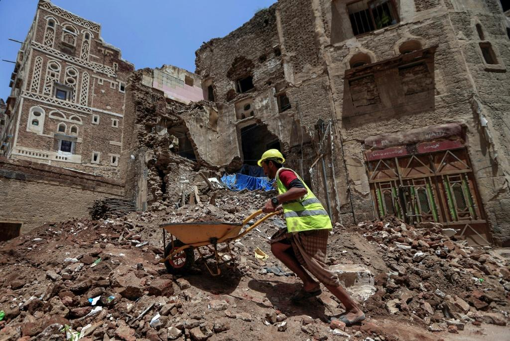 Yemeni labourers remove rubble ahead of restoration works on the site of a collapsed UNESCO-listed building following heavy rains in the Old City of the Yemeni capital Sanaa