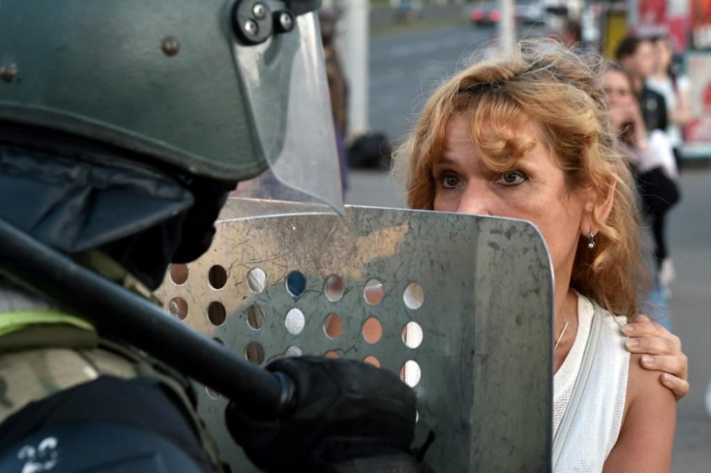 A protesters stares down a Belarus riot police officer during another day of demonstrations against widely-criticised election results