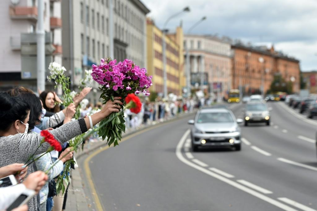 Women with flowers stand along a street as they protest against police violence during recent rallies of opposition supporters, who accuse strongman Alexander Lukashenko of falsifying the polls in the presidential election.