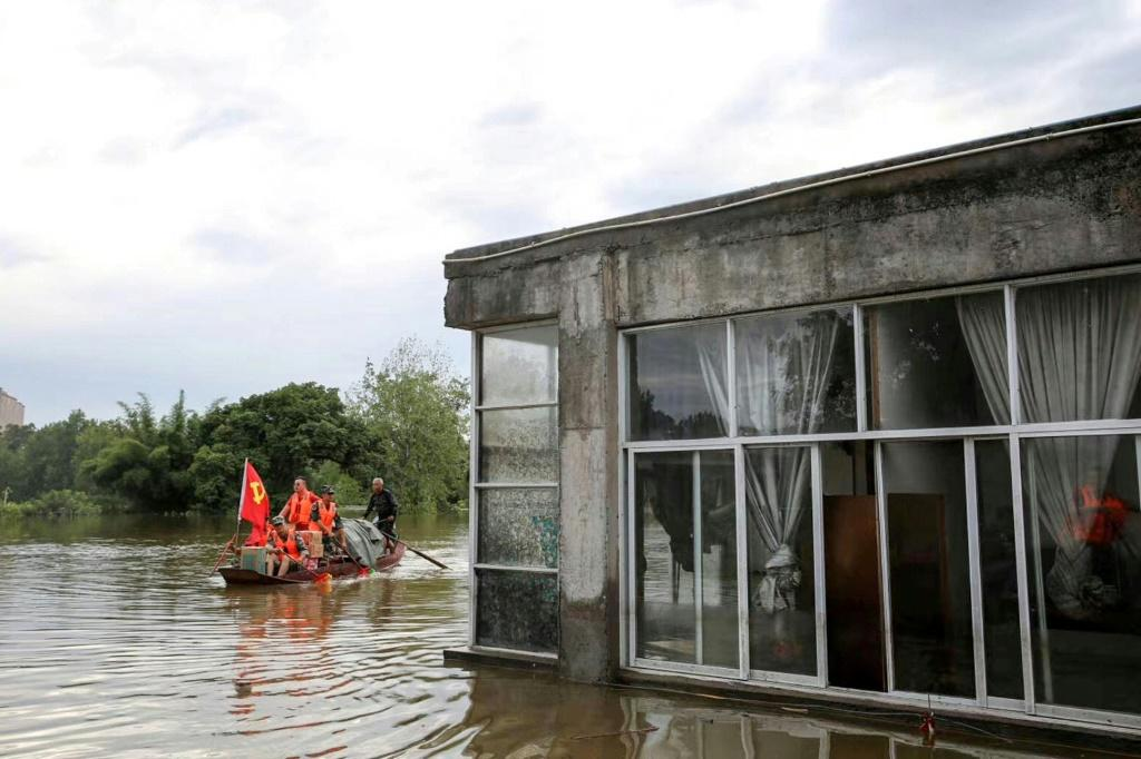 Community workers and volunteers deliver food and supplies to flood-affected residents after heavy rains in Neijiang, Sichuan