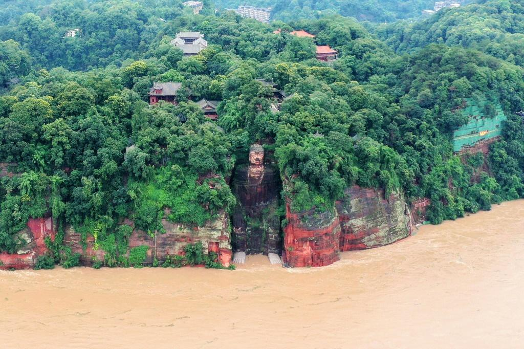 State media footage showed murky floodwaters lapping at the feet of the 71m metre-tall Leshan Giant Buddha in Sichuan - for the first time since the People's Republic of China was founded in 1949