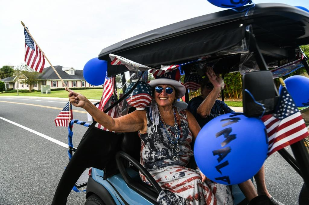 The Villages retirement community in Florida is beset by sharp political divisions -- here a resident rides in a golf cart to celebrate Joe Biden's nomination as Democratic presidential candidate, but not all her fellow seniors agree