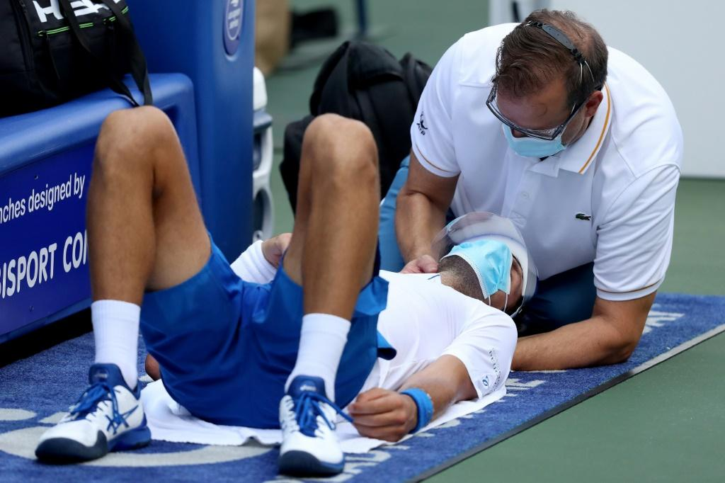 World number one Novak Djokovic received neck treatment from ATP trainer Clay Sniteman, right, but managed to outlast Roberto Bautista Agut in an ATP Western and Southern Open semi-final Friday