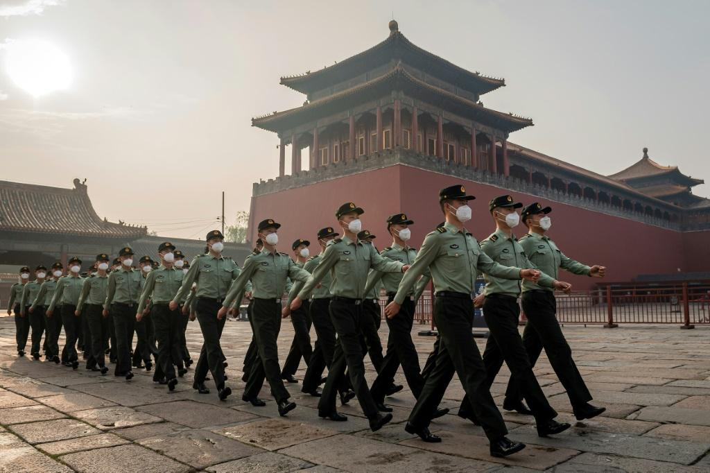 People's Liberation Army (PLA) soldiers march next to the entrance to the Forbidden City in Beijing