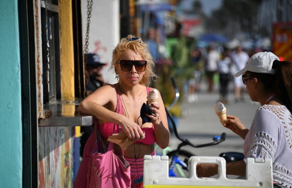 A woman enjoys an ice cream as people come to the beach to escape the heat wave in Venice Beach, California on September 4, 2020.