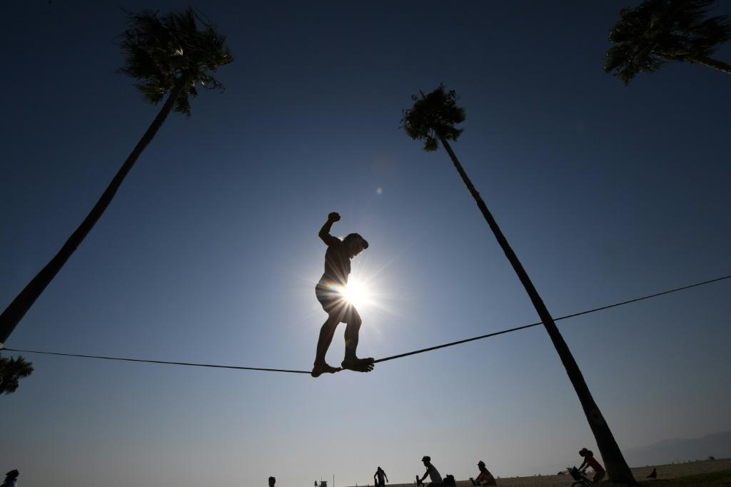 Chuck Reynolds practices his skill on a slack rope in Venice Beach where people flock to the ocean to escape the heat wave on September 4, 2020