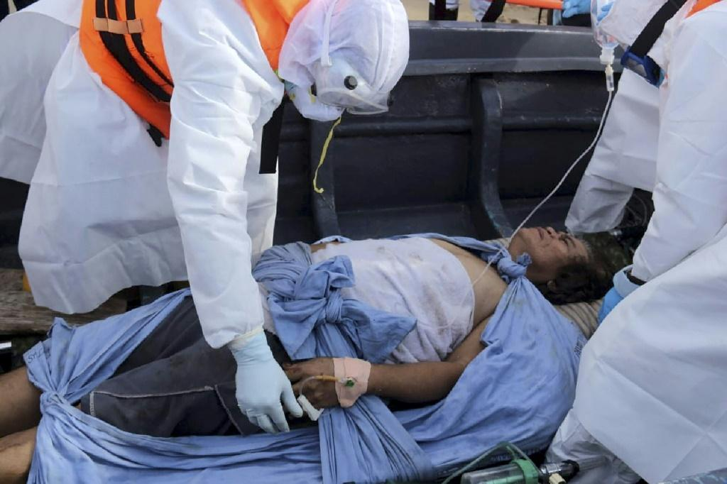 Sri Lankan navy officers carry an injured crewman from the stricken oil tanker, the New Diamond
