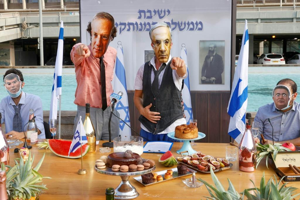 Israeli comedians, wearing masks bearing the portraits of leaders including Prime Minister Benjamin Netanyahu, stage a fake cabinet meeting protesting the government's handling of the Covid-19 pandemic