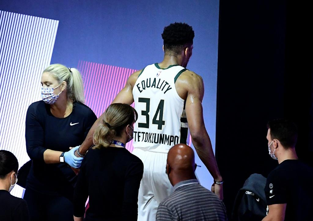 Milawukee star Giannis Antetokounmpo gingerly leaves the court after re-injuring his right ankle in the first half of the Bucks' must-win NBA playoff series game four against the Miami Heat