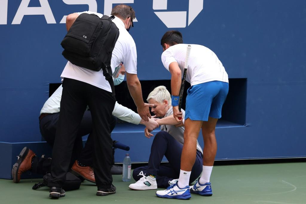Novak Djokovic of Serbia tends to a lineswoman after inadvertently striking her with a ball hit in frustration during his Men's Singles fourth round match against Pablo Carreno Busta of Spain on Day Seven of the 2020 US Open at the USTA Billie Jean King N