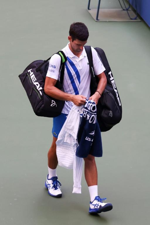 Novak Djokovic of Serbia walks off the court after being defaulted due to inadvertently striking a lineswoman with a ball hit in frustration during his Men's Singles fourth round match against Pablo Carreno Busta of Spain at the US Open