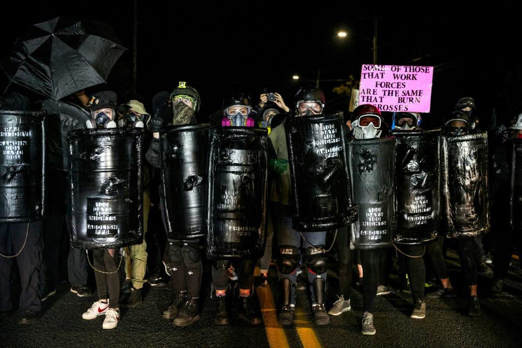 Protestors wearing gas masks and carrying homemade shields demonstrate in Portland, Oregon