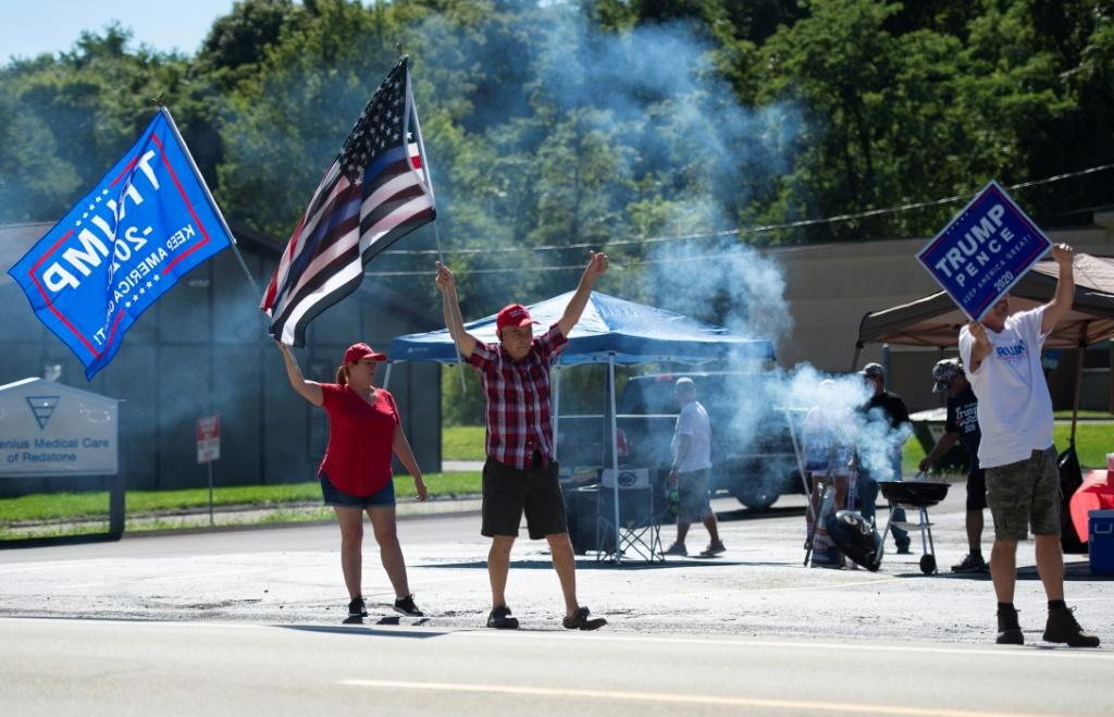 Supporters of US President Donald Trump wield signs and flags as they hold a Republican voter registration in Brownsville, Pennsylvania