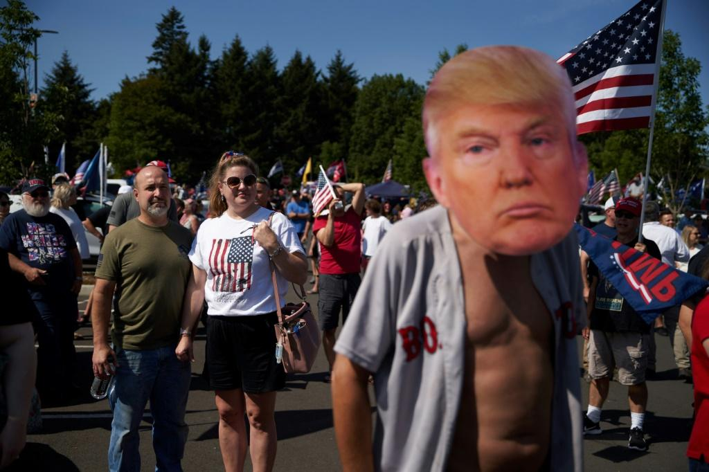 A fan wears a mask depicting President Donald Trump, who is traveling the country to whip up support as polls show him down eight weeks before election day
