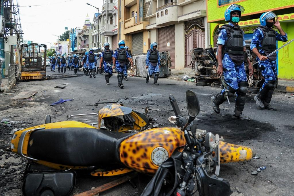 "Rapid Action Force (RAF) personnel patrol on a street of Devara Jevana Halli in Bangalore on August 13, 2020, after a ""derogatory"" Facebook post about the Prophet Mohammed sparked riots"