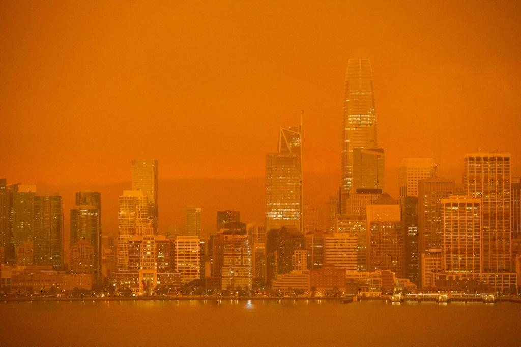 The San Francisco skyline is obscured in orange smoke and haze from the fires