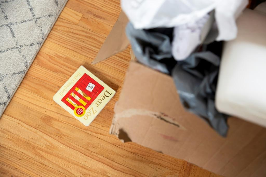 A small child's book lies on the floor next to unpacked boxes in Kyla Brown's new home in El Cerrito, California on September 11, 2020