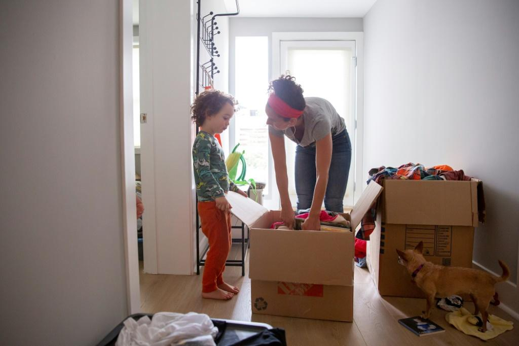 Levi Benjamin-Brown, 5, helps his mother Kyla Brown unpack boxes of toys at their new home in El Cerrito, California, where the family moved from San Francisco