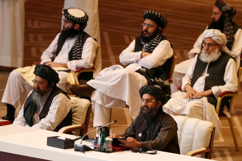 Taliban co-founder Mullah Abdul Ghani Baradar (R, bottom) speaks during the opening session of peace talks with the Afghan government