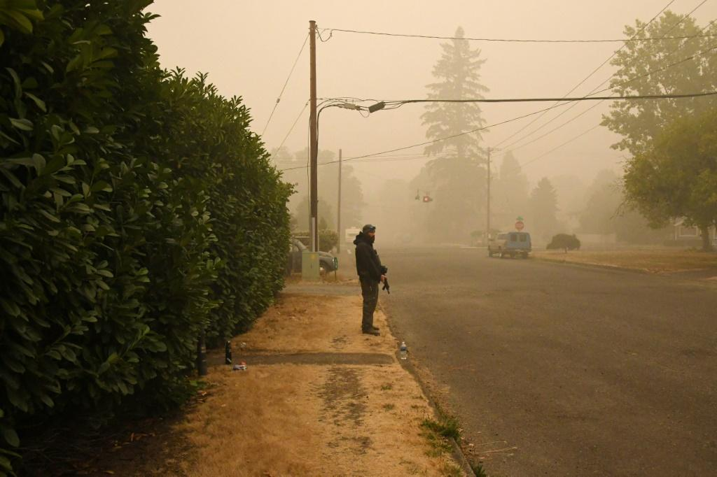 A man stands guard with a firearm outside his home after wildfires and heavy smoke caused many of his neighbors to evacuate the area, in Estacada, Oregon on September 12, 2020