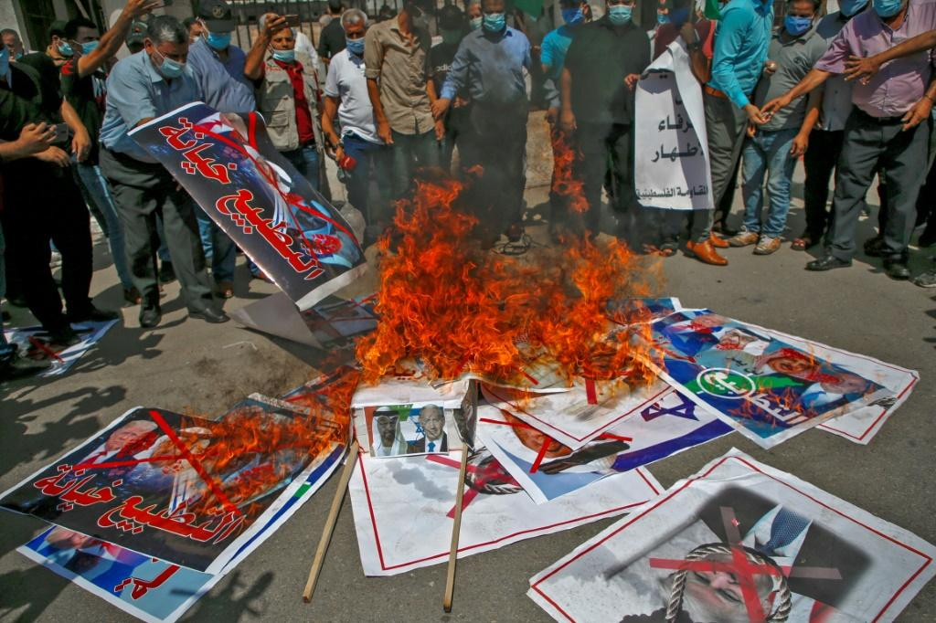 Demonstrators in Gaza City burn pictures depicting leaders of Israel, Bahrain, the United Arab Emirates and the United States to denounce the accords between Israel and Bahrain and the UAE