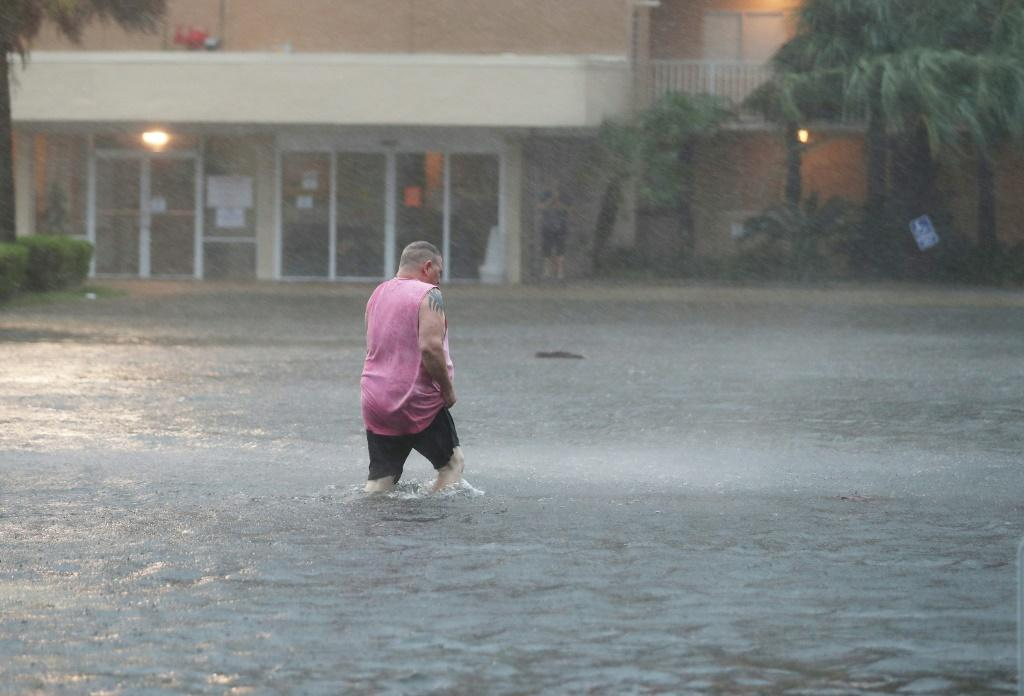 A man walks though a flooded parking lot in Gulf Shores, Alabama