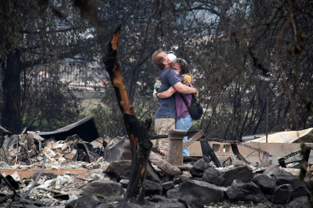Dee Perez comforts Michael Reynolds in the ruins of his home destroyed in the Almeda Fire in Talent, Oregon