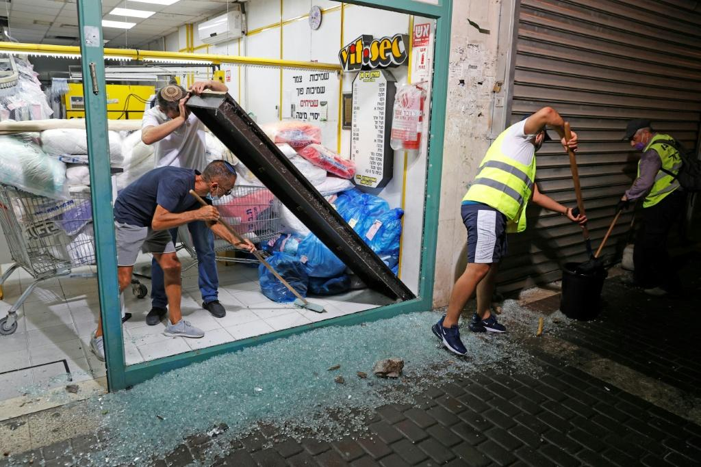 Israeli men remove the shattered glass window of a laundry shop in the southern coastal town of Ashdod following a rocket attack from the Gaza Strip