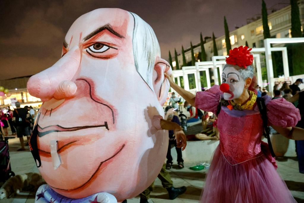 An Israeli woman in a clown's outfit mocks a giant caricature of Prime Minister Benjamin Netanyahu at a protest in Tel Aviv against the second lockdown