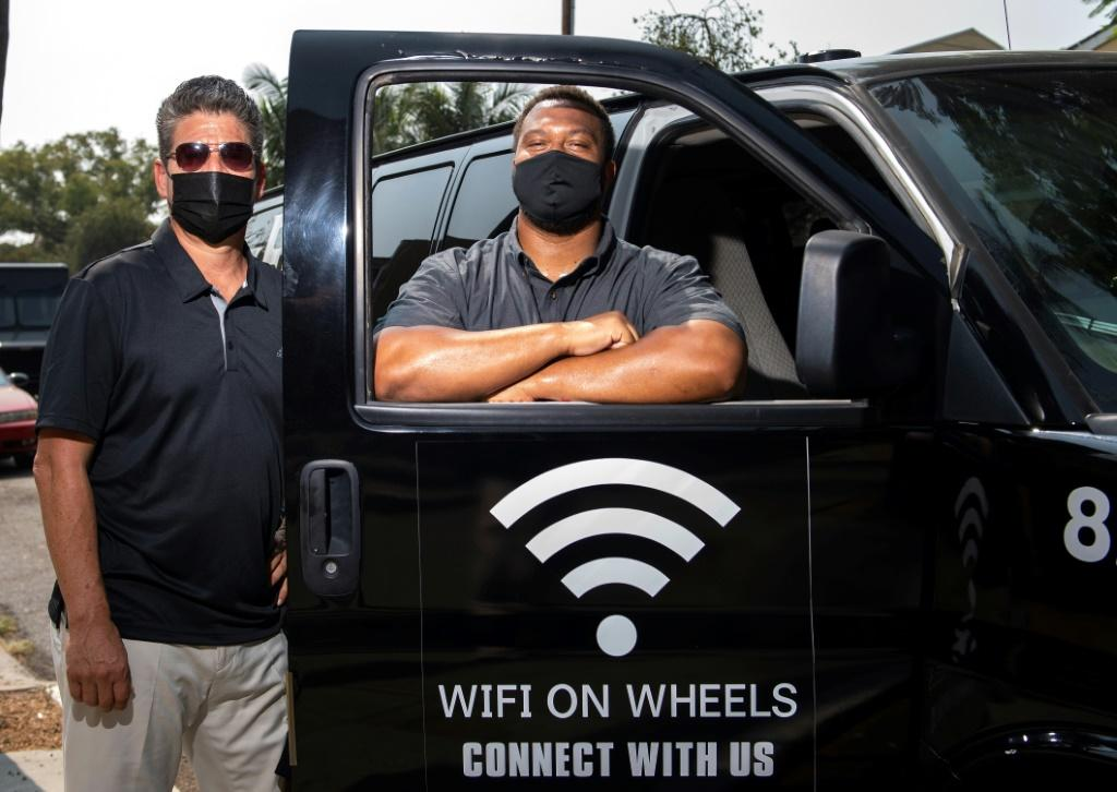 Roman Reyna (L) and Kevin Watson (R), of JFK Transportation, pose by one of their minivans that give underserved kids wifi access in Santa Ana, California