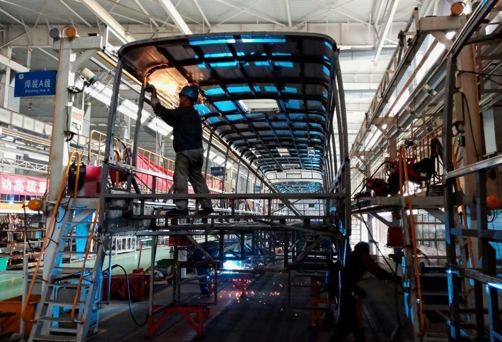 Workers build an electric bus at a factory in Liaocheng in China's eastern Shandong province in December 2018 as the country moves to limit fossil fuel consumption