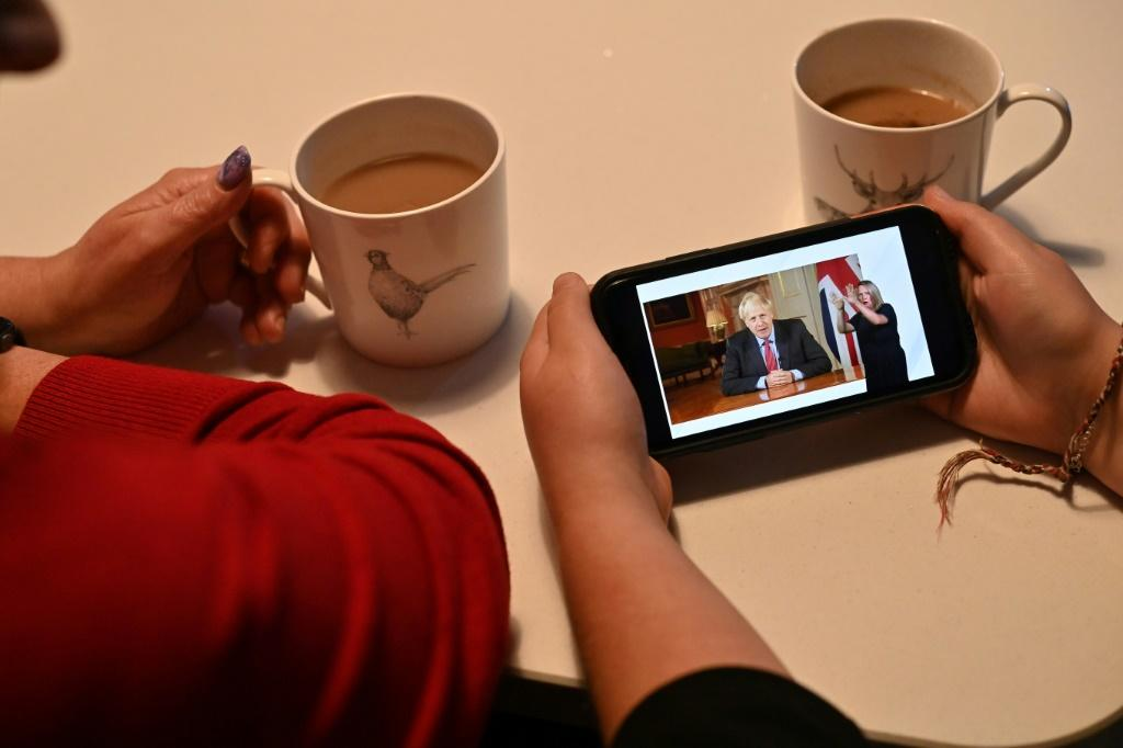 A family watch as Britain's Prime Minister Boris Johnson addresses the nation on Covid-19 restrictions
