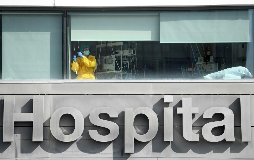 """A healthcare worker looks out the window of La Paz hospital, in Madrid, as Spain's health minister calls on residents of the city to limit their movements and social contacts to the """"essential"""