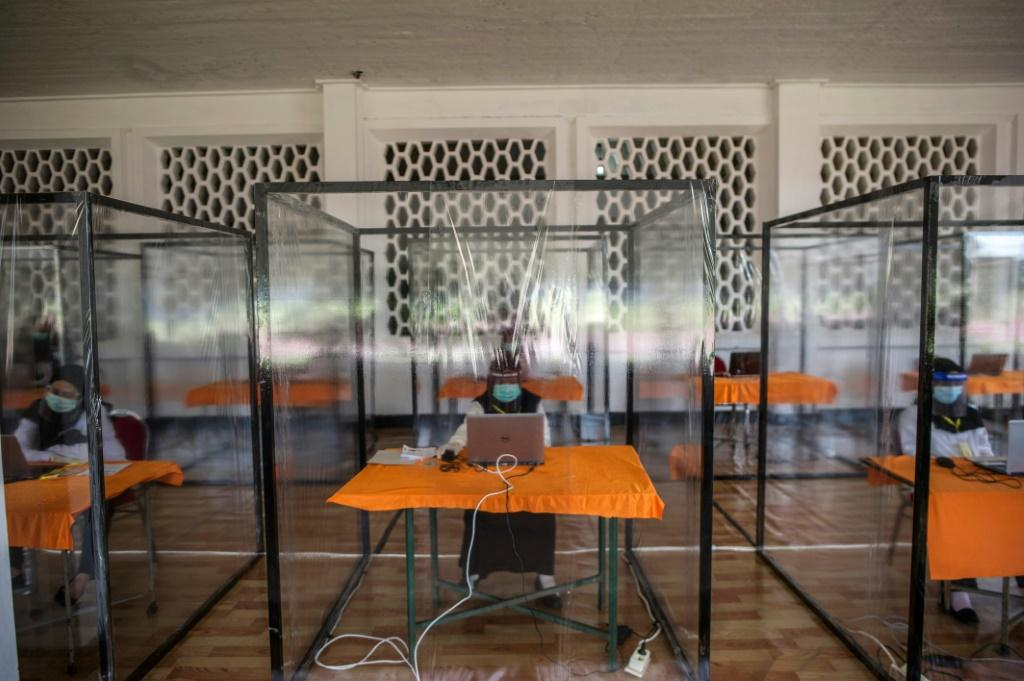 Candidates for Indonesian civil servant jobs sit an exam inside a plastic chamber after they tested positive for COVID-19